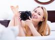 Leinwanddruck Bild - Woman playing with a camera