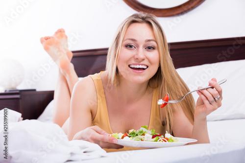 Leinwanddruck Bild Woman in lingerie having a salad