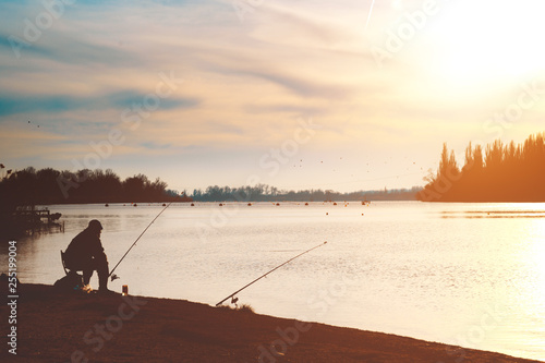 Fisherman with a fishing rod on the river bank. Evening