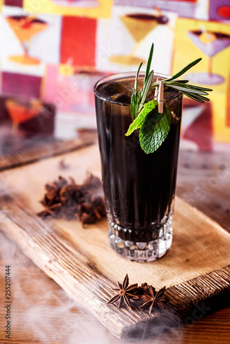 Cocktail with cola or iced tea with cubes decorated with mint and rosemary cocktail in the smoke on a wooden board in the restaurant. copy space, selected focus. © Kirill