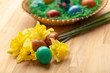 Basket full of colorful easter eggs with flowers by side