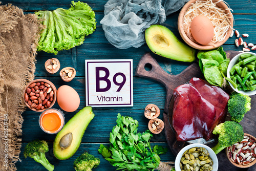 Foods that contain natural vitamin B9: Liver, avocado, broccoli, spinach, parsley, beans, nuts, on a blue background. Top view.