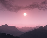 Foggy sunset over mountain landscape.