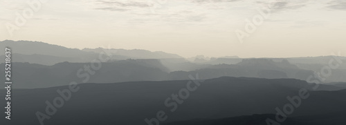 Mountain range in mist under cloudy sky. - 255218637