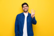 Man with blue jacket over yellow wall happy and counting three with fingers
