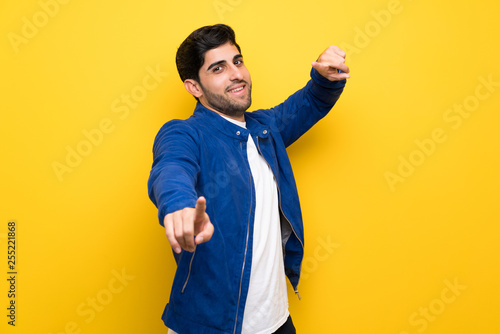 Man with blue jacket over yellow wall points finger at you while smiling