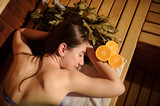 top view of a beautiful woman enjoying massage procedure with oranges and birch broom in a wooden sauna