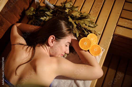 Leinwanddruck Bild top view of a beautiful woman enjoying massage procedure with oranges and birch broom in a wooden sauna