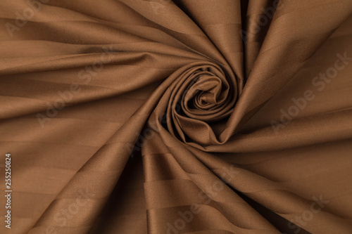 Brown jacquard of sateen weaving is laid by waves in the form of a spiral - 255250824