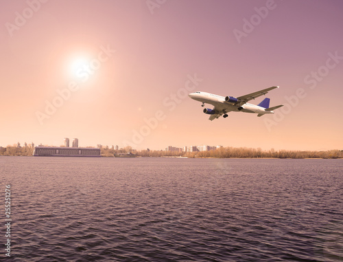 Plane over the river in cloudy weather in the city. Travel, tourism. - 255251276