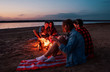 Leinwanddruck Bild - Camp on the beach. Group of young friends having picnic with bonfire