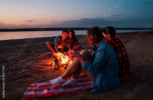 Leinwanddruck Bild Camp on the beach. Group of young friends having picnic with bonfire