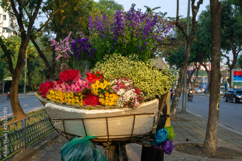 obraz PCV Flower basket on bike of street vendor on Hanoi street. Yellow leaf trees. Autumn or winter season