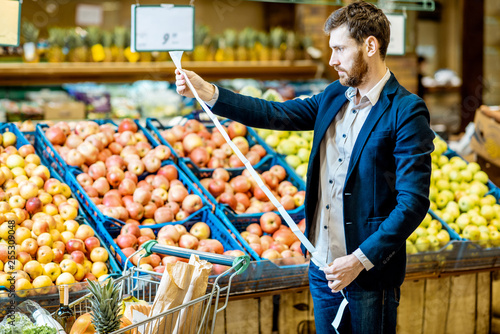 Portrait of an elegant man holding very long shopping list while buying food in the supermarket
