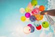 Leinwandbild Motiv Hand holding multi colored balloons done with a retro vintage instagram filter effect.