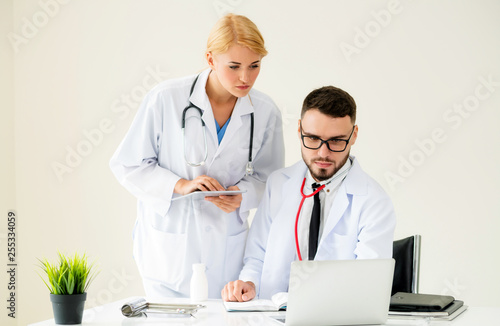 Doctor at hospital office working on laptop computer on the table with another doctor having discussion about patients health.