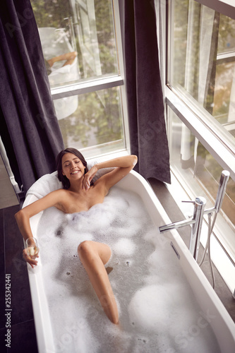 Leinwanddruck Bild Smiling woman relaxing in bath with foam and drink champagne top view.