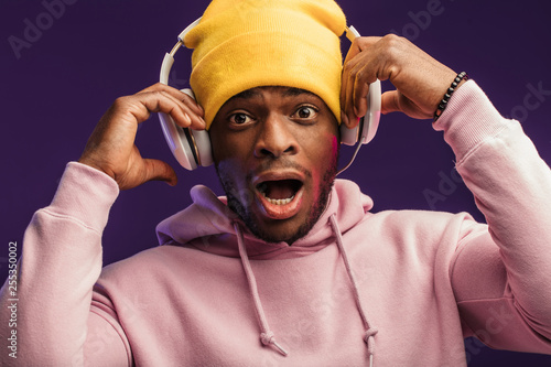 Studio portrait of surprised, shocked DJ, standing open-mouthed with headphones on yellow knitted hat on head looking at camera with disbelief and surprise, omg concept. - 255350002