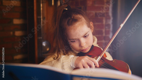 A little girl in white sweater playing violin by notes