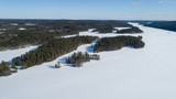 Fototapeta Fototapety na ścianę - Aerial view of beautiful winter lake and forest in National park in Fnland. Winter scenery from above. Landscape photo captured with drone. © raland