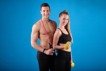 Fitness young man and woman isolated on blue background. © forma82