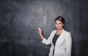 Smiling teacher with chalk on blackboard