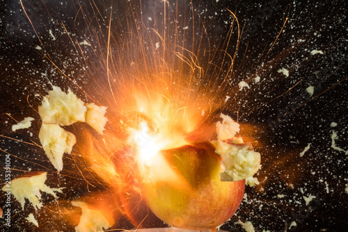 Apple burst into pieces on black background - 255391004