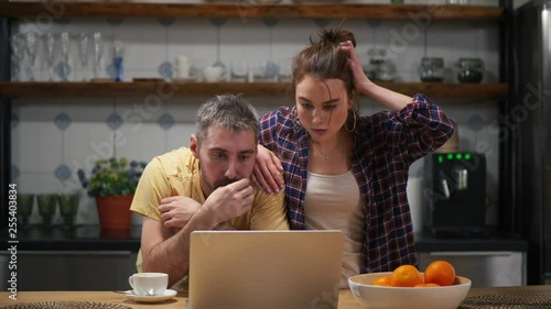 Couple in kitchen tensely watching football on computer. Positive emotions