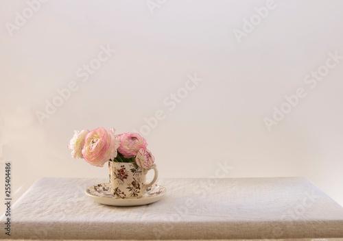 Buquet de flores en taza antigua, fondo y mesa blanco. © carmen