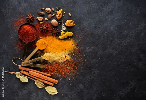 Spice seasoning in metal spoons and copy space for text.