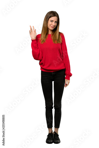 A full-length shot of a Young woman with red sweater saluting with hand with happy expression over isolated white background