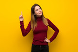 Woman with turtleneck over yellow wall showing and lifting a finger in sign of the best