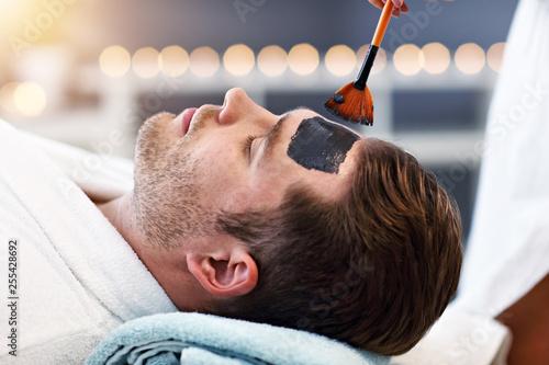 Leinwanddruck Bild Handsome man having facial in spa salon