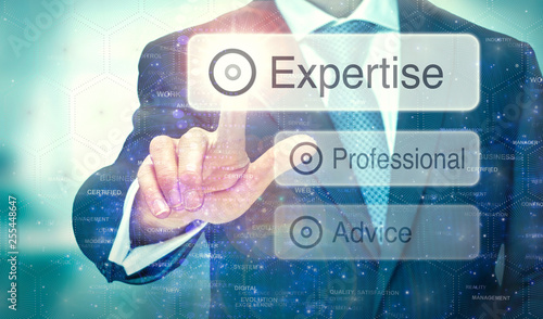 A business man selection a button on a futuristic display with a Expertise concept written on it.