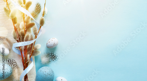 Easter greeting card with colorful easter eggs and sprin flowersl on blue table. Top view with space for your greetings - Image © Konstiantyn