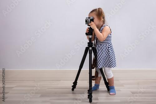 Leinwandbild Motiv Girl Taking Photo With Camera And Tripod