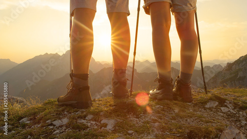 Leinwanddruck Bild CLOSE UP: Active woman and man stand on the mountain peak and watch the sunrise.