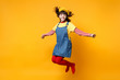 Leinwanddruck Bild - Portrait of smiling cute girl teenager in french beret and denim sundress jumping with flowing hair isolated on yellow wall background in studio. People emotions lifestyle concept. Mock up copy space.