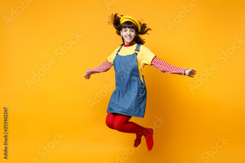 Leinwanddruck Bild Portrait of smiling cute girl teenager in french beret and denim sundress jumping with flowing hair isolated on yellow wall background in studio. People emotions lifestyle concept. Mock up copy space.