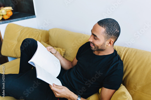 The dark-skinned man is resting on the sofa after work. Handsome guy in a home clothes with interest reading a magazine. Comfort, free time, cosiness, relax.