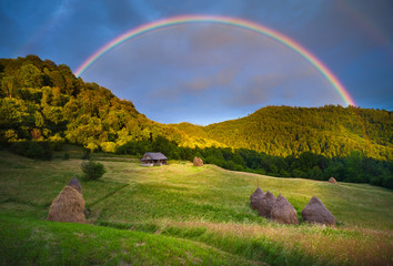 Scenic rainbow landscape on the hills in rural peaceful area
