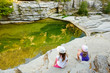 Leinwanddruck Bild - Two cute girls exploring Papingo Rock Pools, also called ovires, natural green water pools located in small smooth-walled gorge near the village of Papingo in Zagori region, Greece.