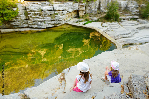 Leinwanddruck Bild Two cute girls exploring Papingo Rock Pools, also called ovires, natural green water pools located in small smooth-walled gorge near the village of Papingo in Zagori region, Greece.