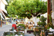 Leinwanddruck Bild - Small outdoor restaurants at the pedestrian area at center of Kalavryta town near the square and odontotos train station, Greece.