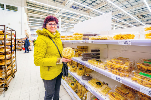 Beautiful mature woman holding a pack of oriental sweets chak-chak. Text in Russian: honey twig, brushwood with sesame