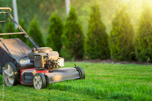 Leinwandbild Motiv Lawn mower cutting green grass