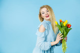 Fototapeta Tulipany - Pretty woman with red yellow tulips bunch © Voyagerix