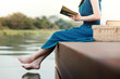 Young Woman Relaxing by Riverside. Sitting on Deck and Reading Book. Unplugged Life Concept