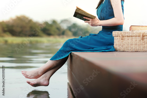 fototapeta na ścianę Young Woman Relaxing by Riverside. Sitting on Deck and Reading Book. Unplugged Life Concept