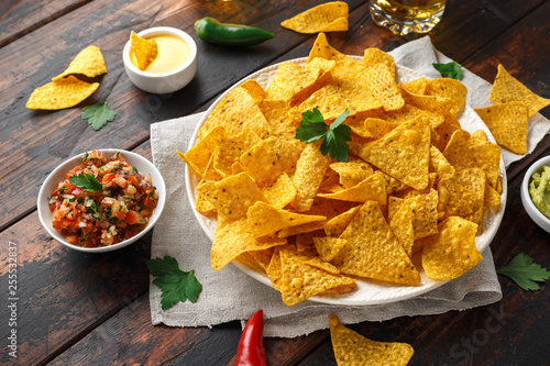 Tortilla nachos chips with cheese sauce, guacamole and tomatoes salsa dip. glass of beer. - 255532837